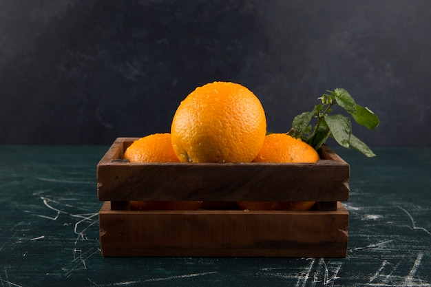 Gelbe orangen mit grünen blättern in einer holzkiste mit wassertropfen darauf