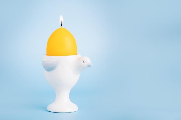 Gelbe ostern brennende eierkerze in einer vogelform-eierschale