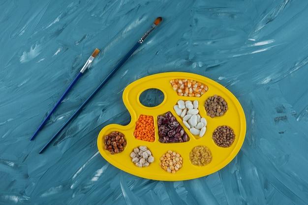 Gelbe palette verschiedener bohnen- und linsensorten mit pinseln.