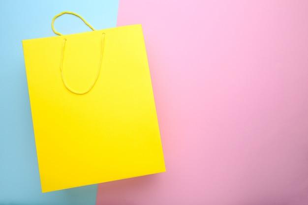 Gelbe papiereinkaufstasche auf buntem hintergrund