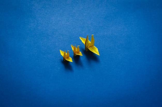 Gelbe papiermutter und babyvögel auf blauem hintergrund. minimales muttertagskonzept.