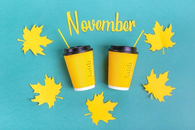 Gelbe papiertassen kaffee und herbstlaub, text november schnitten vom papier auf blau heraus