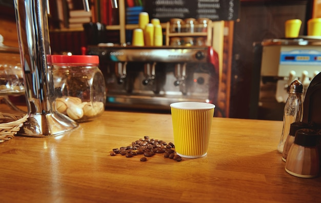 Gelbe pappbecher mit heißem kaffee und verstreuten gerösteten bohnen auf einem holztisch auf dem hintergrund der kaffeemaschine
