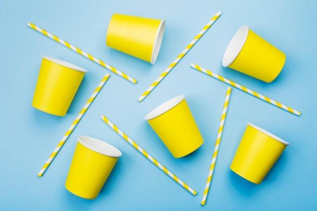 Gelbe pappbecher und gelb-weißes stroh auf blau. ansicht von oben