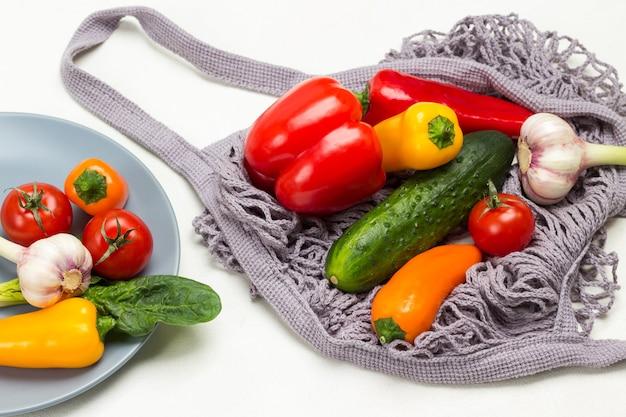 Gelbe paprika, knoblauch und rote tomaten auf grauer platte. gurken und paprika in grauem netz. weißer hintergrund. ansicht von oben
