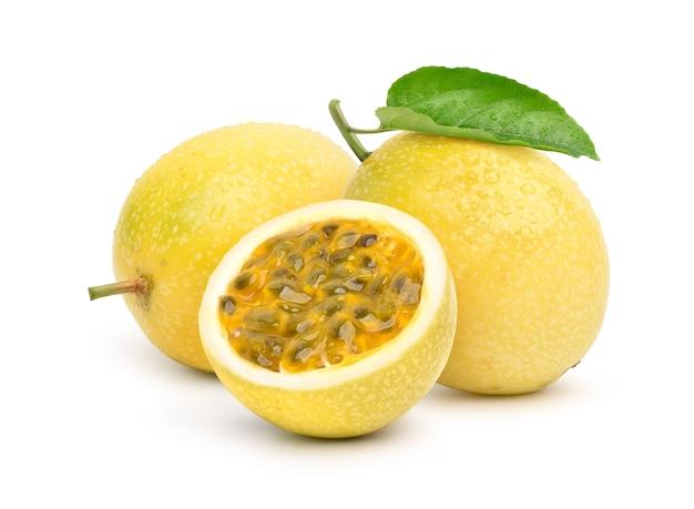 Gelbe passionsfrucht mit halbiertem schnitt und grünem blatt isoliert