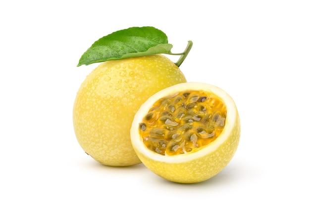 Gelbe passionsfrucht mit halbiertem und grünem blatt lokalisiert auf weißem hintergrund. beschneidungspfad.