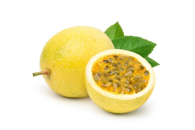 Gelbe passionsfrucht mit halbiertem und grünem blatt lokalisiert auf weißem hintergrund.
