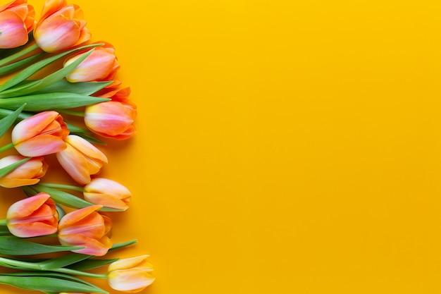 Gelbe pastelle färben tulpen auf gelbem hintergrund. retro-vintage-stil. stillleben, flache laienkunst.