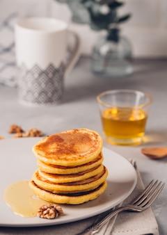 Gelbe pfannkuchen mit maismehl und kurkuma, gekleidetem honig und roten trauben