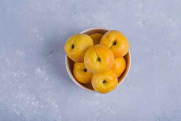 Gelbe pfirsiche in einer weißen keramikschale in der mitte des tisches