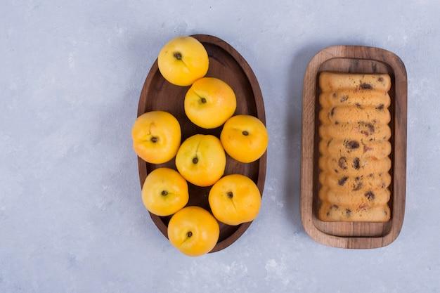 Gelbe pfirsiche und rollkuchen in holzplatten in der mitte des tisches