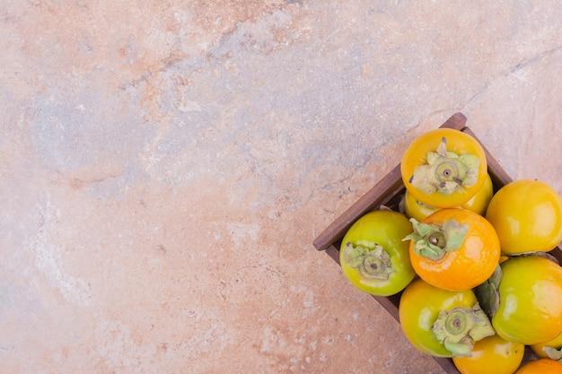 Gelbe pflaume datiert in einem holztablett