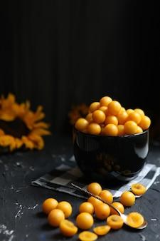 Gelbe pflaumen auf schwarzem hintergrund. zutaten für eine marmelade. food-fotografie. vertikales bild. gelbe sonnenblume, herbstkonzept, ernte.