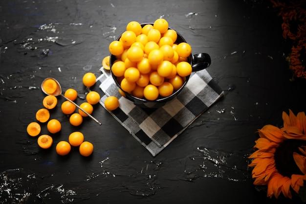 Gelbe pflaumen mit zitrone und limette auf schwarzem hintergrund. zutaten für eine marmelade. food-fotografie. gelbe sonnenblume, herbstkonzept,