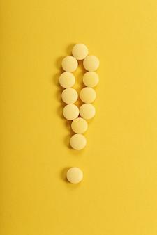 Gelbe pillen auf gelber oberfläche