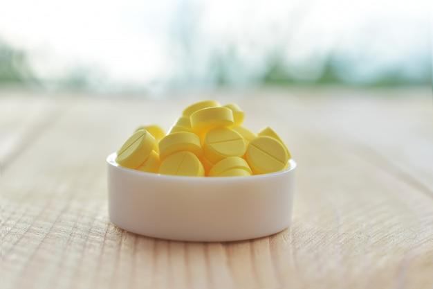 Gelbe pillen auf hölzerner tabelle
