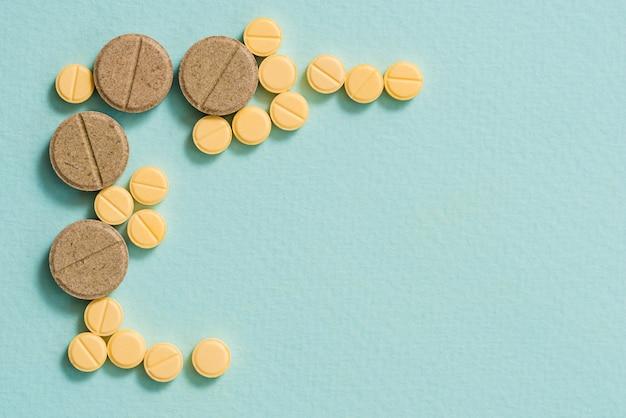 Gelbe pillen und kapseln auf einem blauen hintergrund. offene kapsel, pulverisierte medizin