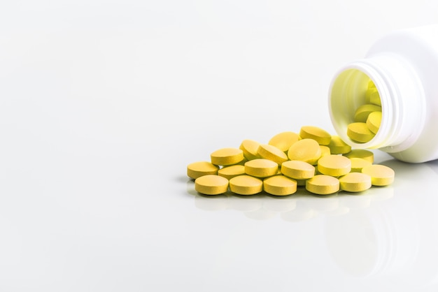 Gelbe pillen werden von einem glas auf einem weißen hintergrund zerstreut
