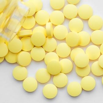 Gelbe pillen zerstreuten von einem glasgefäß auf weiß