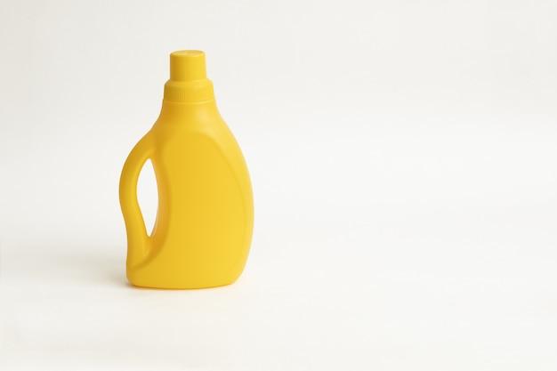 Gelbe plactic flasche für reinigungsmittel auf einem weißen backgraund