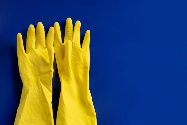 Gelbe plastikhandschuhe an der blauen wand