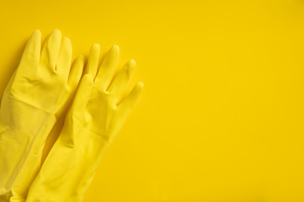 Gelbe plastikhandschuhe an der gelben wand