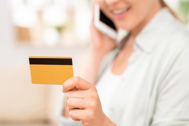 Gelbe plastikkarte mit schwarzer magnetlinie in der hand des jungen weiblichen verbrauchers, der durch smartphone spricht