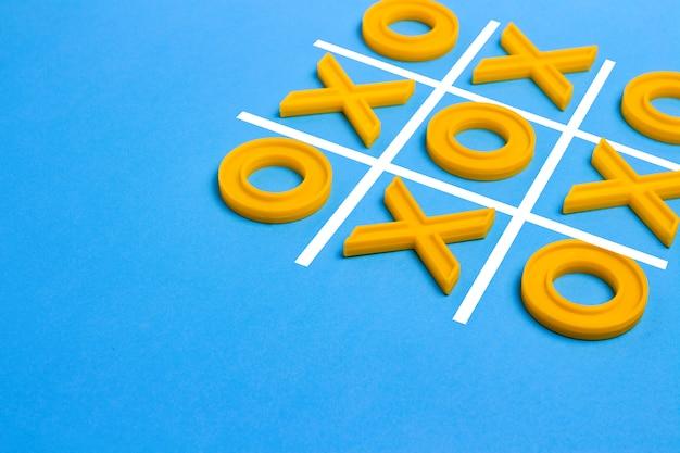 Gelbe plastikkreuze und ein zeh und ein regelfeld zum spielen von tic-tac-toe auf blauem hintergrund. concept xo win challenge. lernspiel für kinder