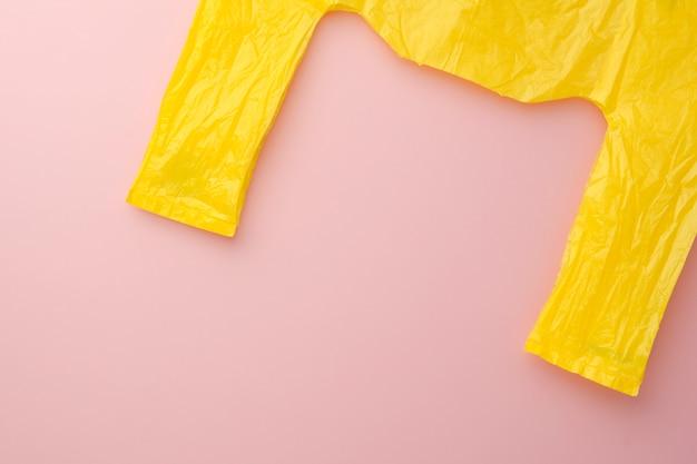 Gelbe plastiktüte auf dem rosa hintergrund