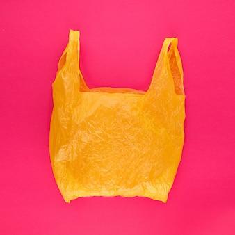 Gelbe polyethylen-tasche auf lebendigem rosa abstraktem hintergrund
