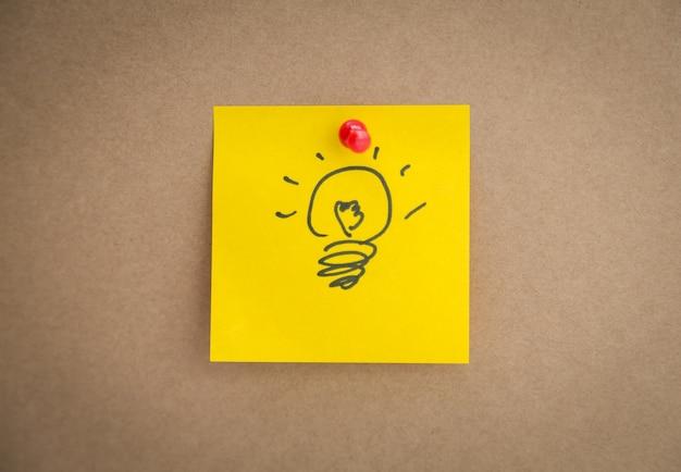 Gelbe post-it mit gezogenem glühbirne
