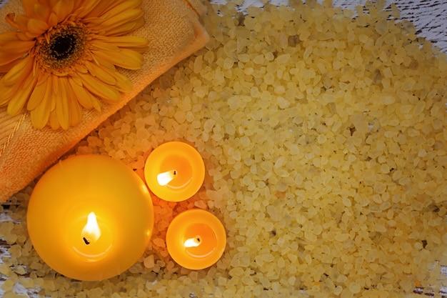 Gelbe produkteinstellung des badekurortes. seesalz, -tuch und -kerzen auf dunklem hölzernem hintergrund