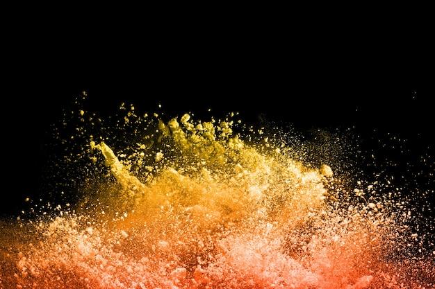 Gelbe pulverexplosion auf schwarzem hintergrund