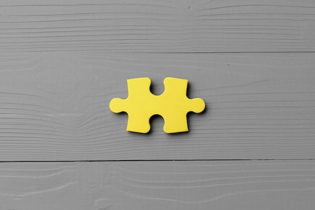 Gelbe puzzleteile auf grauem nahaufnahmekopierraum
