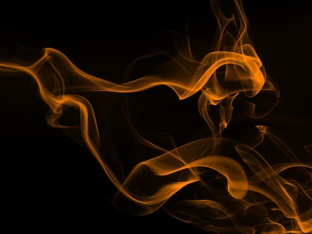 Gelbe rauchabstraktion auf schwarzem hintergrund, feuerentwurf