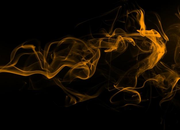 Gelbe rauchzusammenfassung auf schwarzem hintergrund, feuer