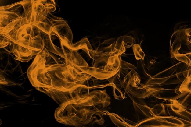Gelbe rauchzusammenfassung auf schwarzem hintergrund, gelbe tinte auf dunkelheit