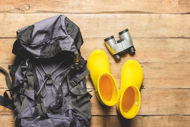 Gelbe regenstiefel, rucksack, fernglas, campingausrüstung auf einem hölzernen hintergrund. das konzept von wandern, tourismus, camp, bergen, wald. banner. flache lage, draufsicht