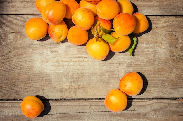 Gelbe reife saftige aprikosen auf hölzernem hintergrund. selektiver fokus.