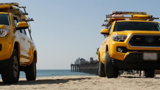 Gelbe rettungsschwimmer auto, oceanside beach, kalifornien usa. küstenrettungs-rettungsschwimmer holen lkw, lebensretterfahrzeug ab. kultige auto- und ozeanküste. los angeles vibes, sommerliche ästhetische atmosphäre.