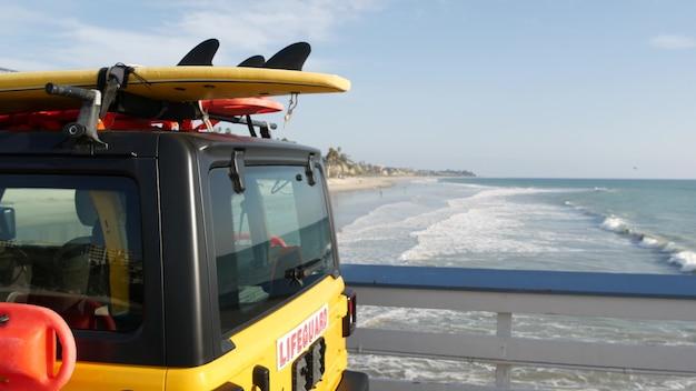 Gelbe rettungsschwimmer auto, san clemente beach pier, kalifornien usa. küstenrettungs-rettungsschwimmer holen lkw, lebensretterfahrzeug ab. auto- und ozeanküste. los angeles vibes, sommerliche ästhetische atmosphäre.