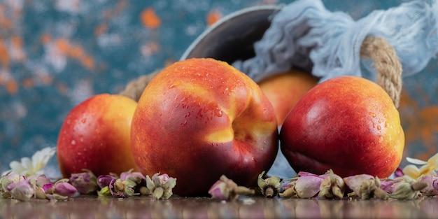 Gelbe rötliche pfirsiche auf einem stück sackleinen auf dem tisch.