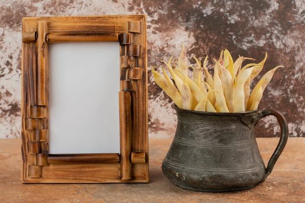 Gelbe rohe bohnen in schüssel und bilderrahmen.