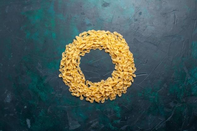 Gelbe rohe nudeln italienische nudeln der draufsicht auf dem dunkelblauen hintergrund