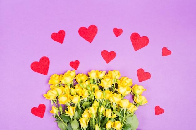 Gelbe rosa rosenblumen mit roten herzen auf lila tischhintergrund