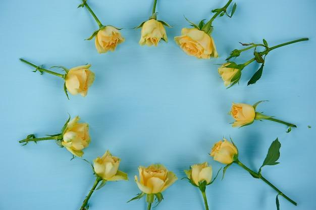 Gelbe rosen auf blauer oberfläche