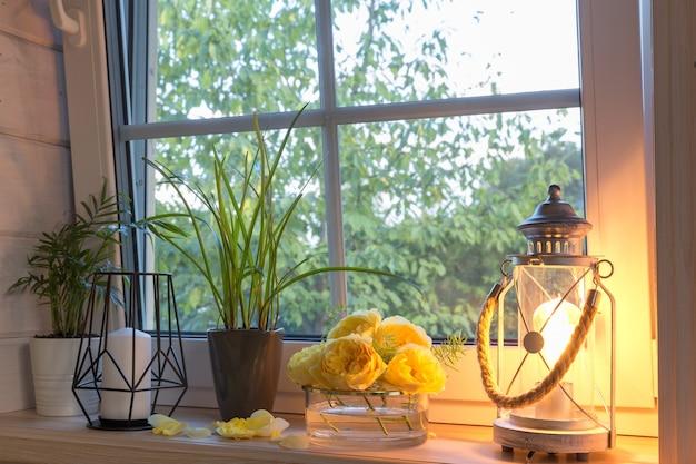 Gelbe rosen auf der fensterbank, kerzen, herbstblätter, laterne.