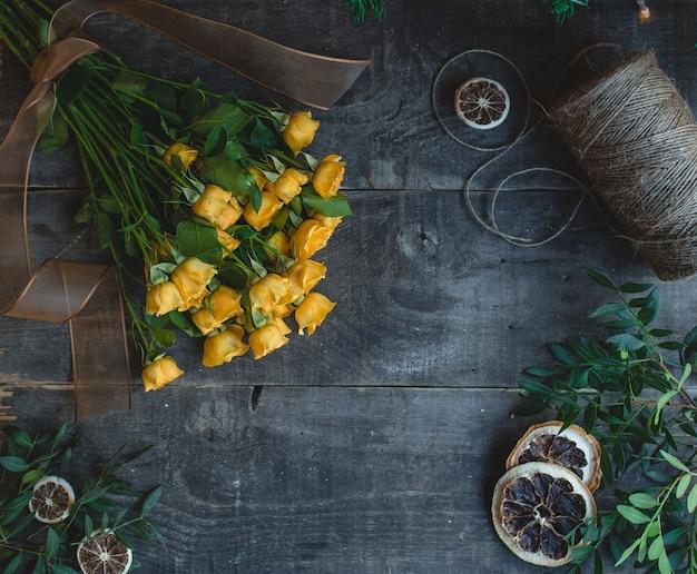 Gelbe rosen auf einem dunklen holztisch mit getrockneten orange scheiben.