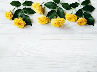 Gelbe Rosen auf einem hellen hölzernen Hintergrund